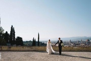 Coppia di sposi per mano con alle spalle il meraviglioso panorama di Firenze